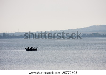 A small boat with people fishing in the middle of the lake during autumn (fall).