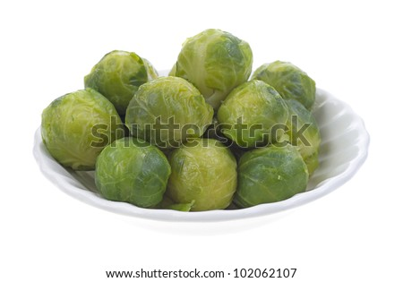 A small bowl filled with freshly cooked Brussels sprouts on a white background.