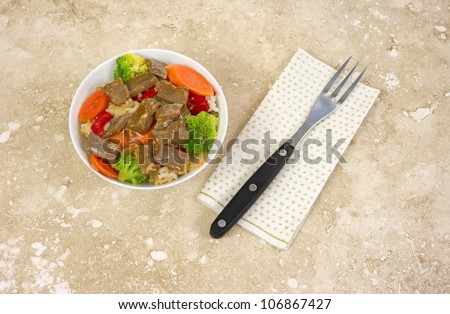 A small bowl of beef teriyaki with vegetables and a fork on paper napkin atop a marble tabletop.