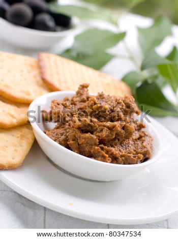 A small bowl of tapenade or olive paste with  crackers. Selective focus