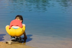 A small boy playing at the shore of lake