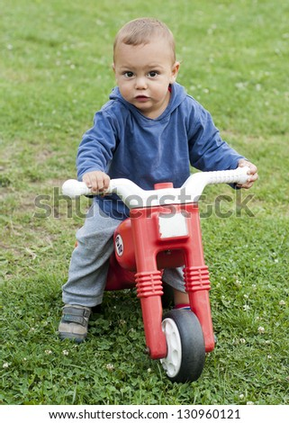 A small boy playing outside with a plastic toy motorbike. - stock photo
