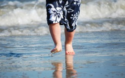 A small boy running bare foot in the water on a beach with waves crashing behind him on a hot sunny day