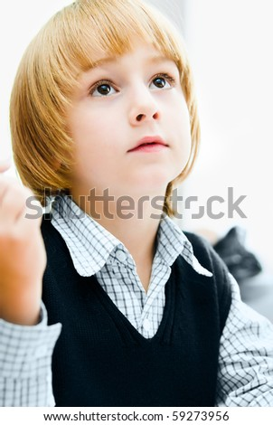 A small boy sits at the desk