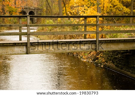 "A small bridge marked ""No swimming or wading"" crosses a small stream in park full of autumn foliage."