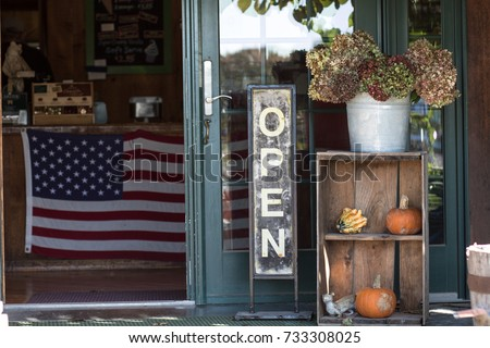 A small business is open for business with a welcoming open sign, pumpkins and dried flowers. Inside the store hangs an American flag.