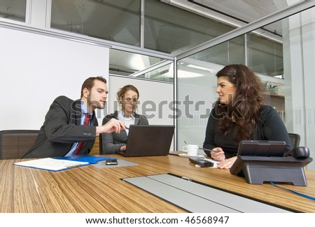 A small business team in a cubicle conference room during a meeting
