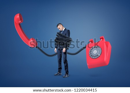 A small businessman stands bound by a huge plastic cord from a giant red retro phone. Always online. Business communication. Old-fashioned business tech.