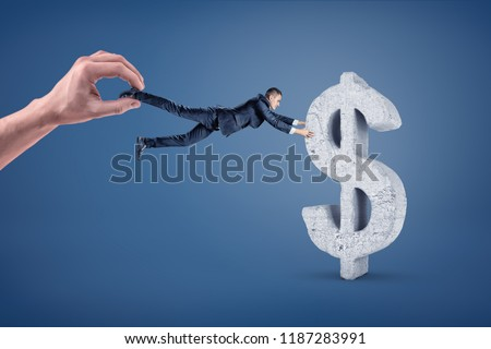 A small businessman tries to hold and grab a big concrete dollar sign while a giant hand tugs him away. Currency contract. Stable dollar. Savings and stability.