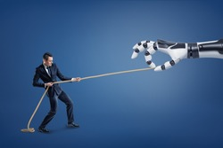 A small businessman tugs a long rope competing with a giant robotic hand. Tug of war. Business and technologies. Human vs machine.