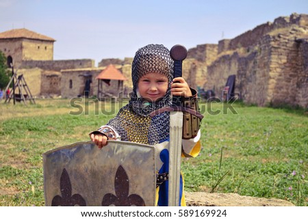 Stock Photo a small but very brave girl in armour and chain mail with sword and shield in a medieval castle