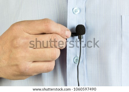 A small buttonhole microphone on a man's shirt. The man fixed the mini microphone to his blue shirt. Lavalier microphone