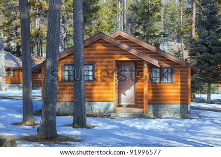 A small cabin constructed of logs in a forested setting.