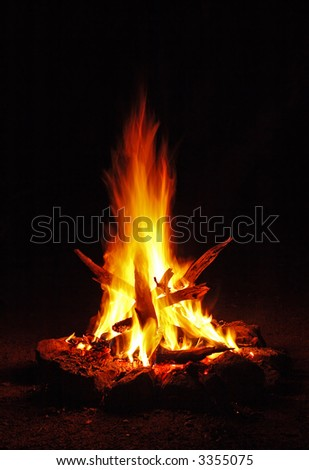 A small campfire built outdoors for people to sit around