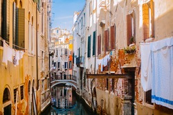 A small canal street in Venice. Old houses with Windows facing the canal. Italian flavor in Venice. Clothes drying on a clothesline in the street Tourist destination Venice, Italy.