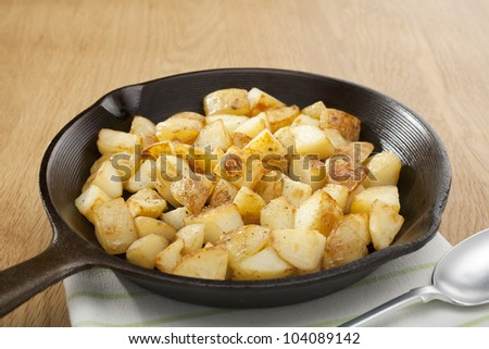 A small cast iron skillet or frying pan filled with home fries or saute potatoes.