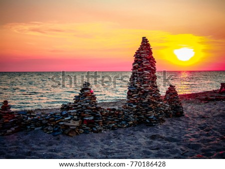a small castle from the coastal pebbles on the background of a beautiful sunset, built by the tourists on the seafront