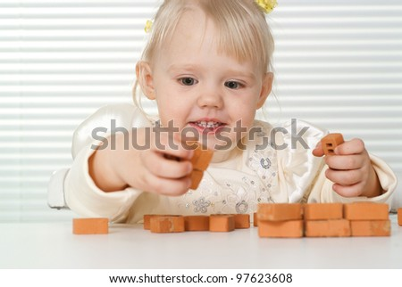 A small charming Caucasian baby sitting at the table and plays with the designer on a light background