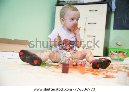 A small cheerful blonde boy with spots of paint on his body tastes the paint by pressing his palm to his mouth, sitting on a large sheet of paper covered with colored stains, blots and blots #776806993