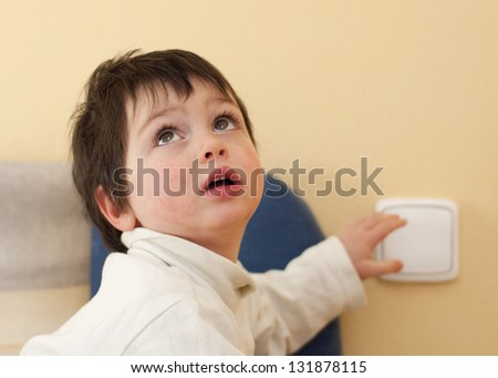 A small child, boy or girl, looking up and reaching to a light switch.