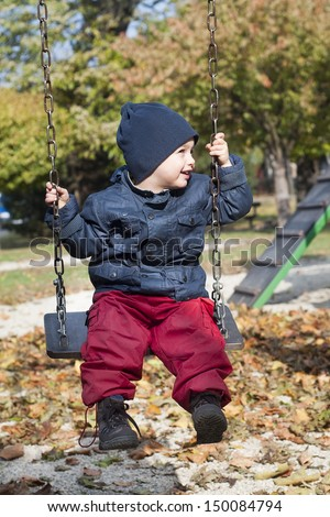 A small child, boy, playing on a swing in a playground in the autumn or fall.