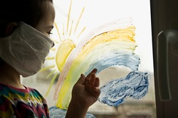 A small child draws a colored rainbow on a glass window. The kid at home on self-insolation during quarantine looks at the village through a painted rainbow on glass