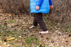 a small child goes barefoot on dry grass and leaves in the forest in spring