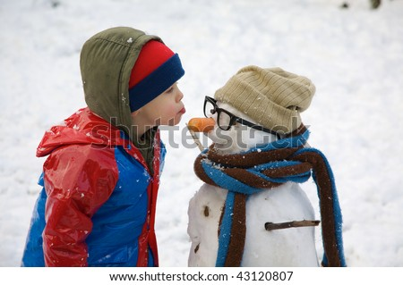 A small child is about to give his snowman a kiss!