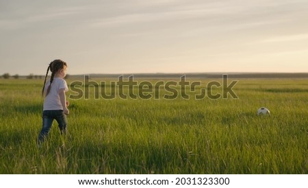 A small child kicks the ball on the field at sunset, a FIFA World Cup fan, a kid running on green grass dreaming of becoming a football player, preparing a baby for an adult final game