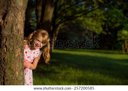 a small child playing in the forest peeps out from behind a tree