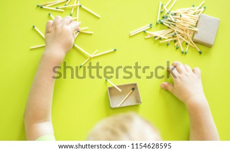 A small child plays with matches, matches matches into boxes, close-ups, fire, lucifer match, hand #1154628595