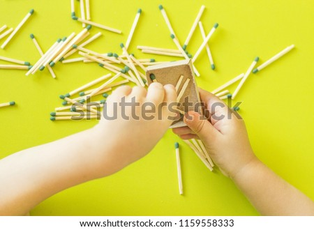 A small child plays with matches, matches matches into boxes, close-ups, fire, lucifer match, hand #1159558333