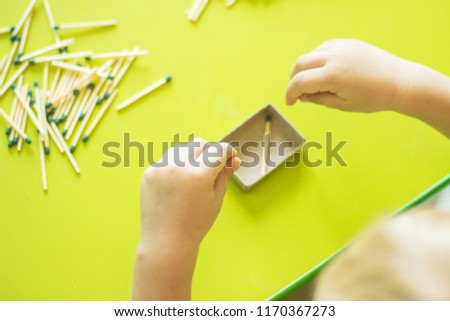 A small child plays with matches, matches matches into boxes, close-ups, fire, lucifer match, hand #1170367273