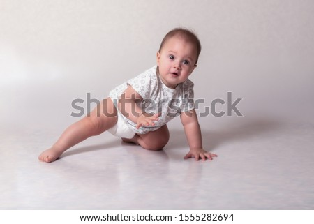 A small child rests on his left knee and left palm. Her right leg is set aside. Her right hand is raised up. #1555282694