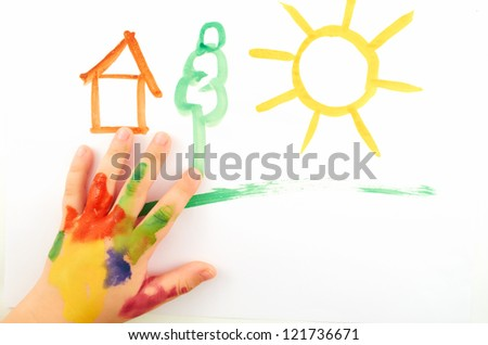 A small child's hand soiled in paints draw  a picture
