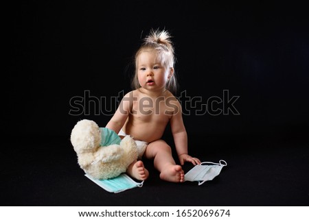a small child sits next to a sick teddy bear. the concept Foto stock ©