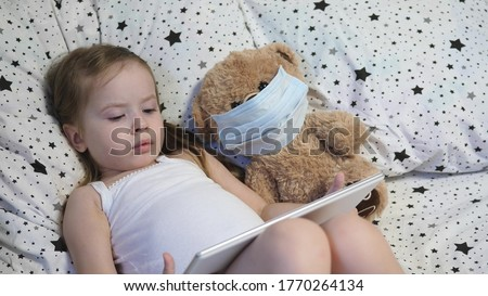 A small child with a bear in a mask plays a tablet while lying on the bed. Kovid-19. Kid is quarantined at home. Distance learning for preschoolers. Modern technologies. Stok fotoğraf ©