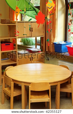 A small children's table with children's chairs in front of a shelf with toys