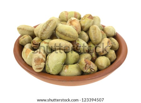 A small clay bowl filled with edamame soybeans on a white background.