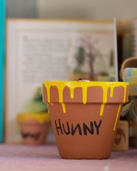 A small clay pot dripped with yellow paint and