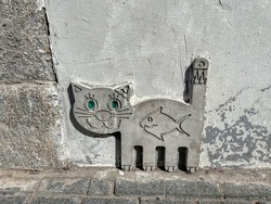 A small concrete bas-relief depicting a kitten with a fish by the road. Sculpture of a cat on the street of St. Petersburg. The cat indicating the location of the attraction - the cat-courtyard.