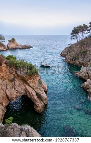 a small cove with crystalline waters and with a small cave, a small boat is sailing in it with three people, Cala de Sa Foradada, Palamos, Costa Brava, Girona, Spain Foto stock ©