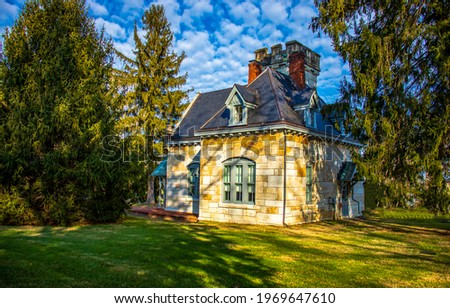 A small cozy house in the shade of trees. Lodge among the trees. A small house with a green lawn