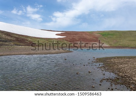 A small crater lake, a patch of ice, volcanic soil and fresh grass. A scene from Geghama mountains of Armenia #1509586463