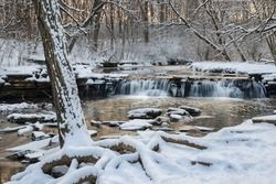 A small creek tumbles over a waterfall as warm light from a setting sun reflects off the icy waters.