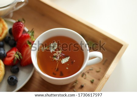 a small cup of aromatic tea with herbs on a wooden tray and cheesecakes with fresh berries Сток-фото ©