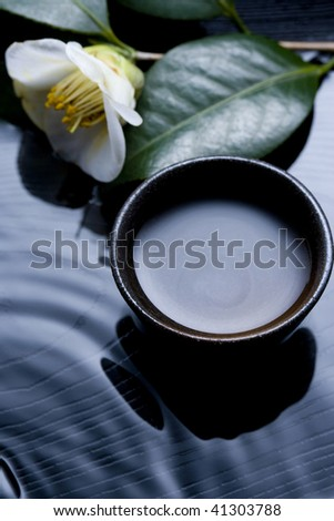 A small cup of sake and white camellia on the black square lacquer plate