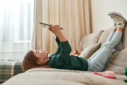 A small cute girl playing games on a tablet lying on a sofa with her feet up and gumshoes on in a big room being alone at home. Children and modern technologies