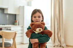 A small cute girl tightly holds her fluffy toy while looking into a camera stainding in a spacy kitchen being at home alone