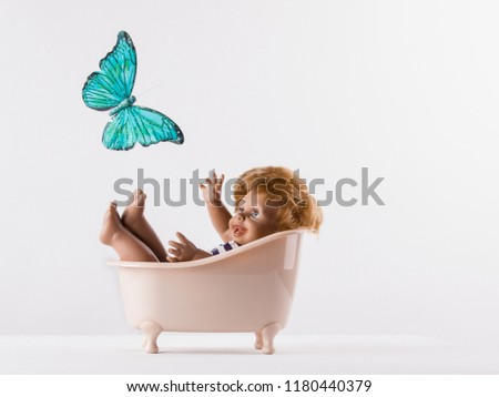 A small doll-boy lies in the bathroom on a white background and looking at a beautiful flying butterfly